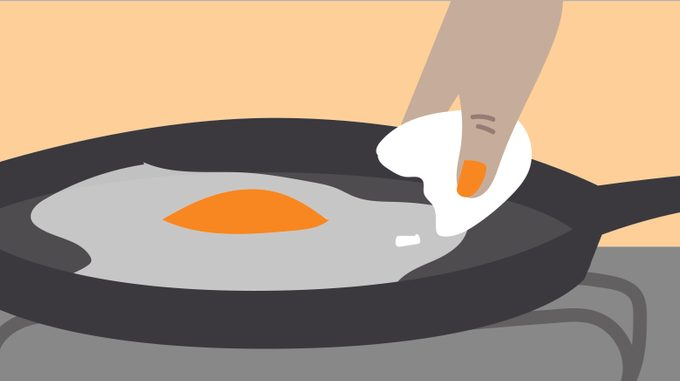 Person cracking an egg into a skillet
