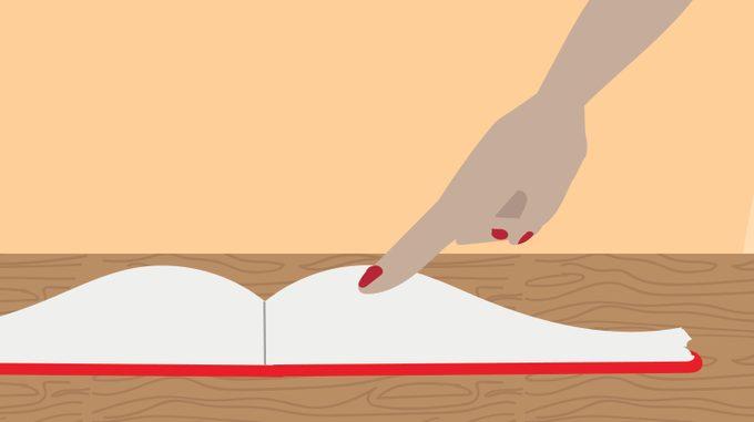 Person running their finger over an open recipe book