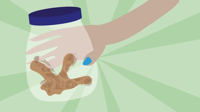 Hand around a glass jar with garlic inside