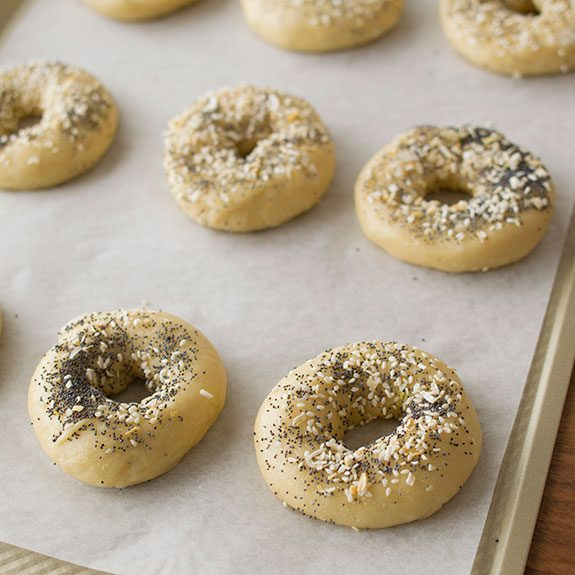 Freshly made bagels lined up on a lined baking sheet and topped with seasonings