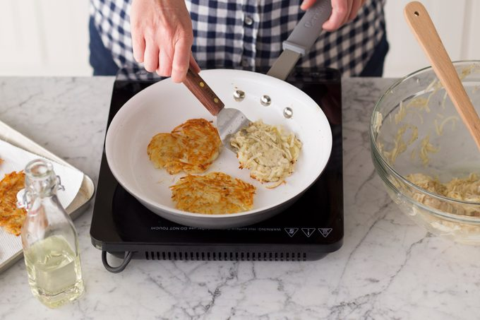 Metal spatula flipping potato pancakes as they fry in a skillet