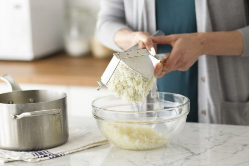 Person using a potato ricer to mash their potatoes and letting them fall into a glass bowl