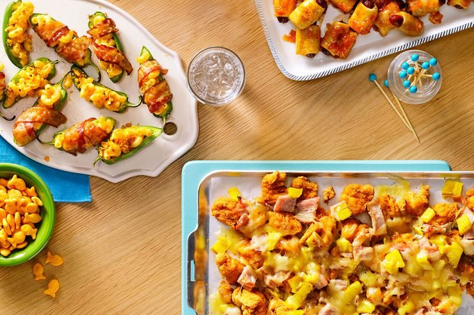Table with plates of pigs in blankets, cheesy chicken tenders, goldfish crackers and sliced jalapenos wrapped in bacon and mac and cheese