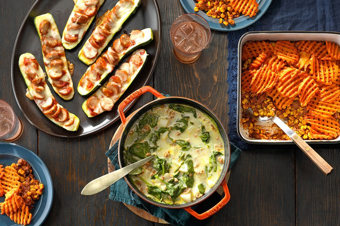 Plates of food crowded onto a table which includes potato soup, sliced zucchinis covered in sausage and a casserole with waffle fries