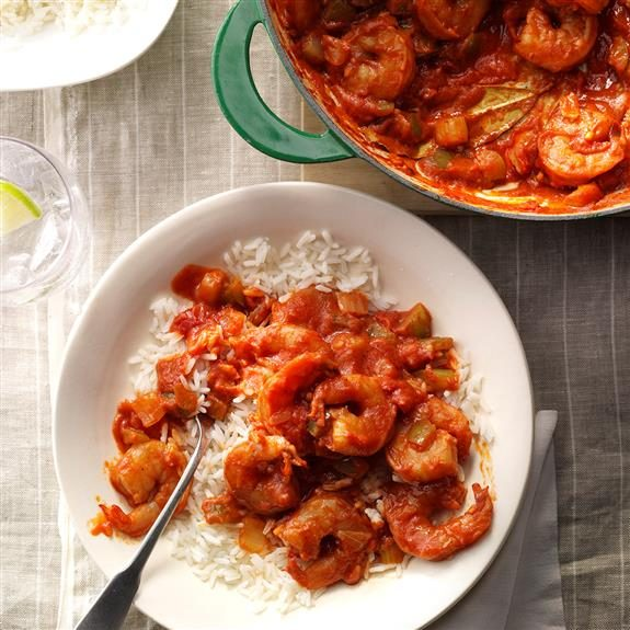 Shrimp creole in a green pot and over rice on a separate plate with a spoon dug into it