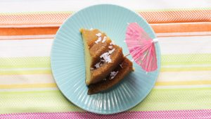 Slice of coconut rum cake on a bright blue plate with a tiny pink umbrella