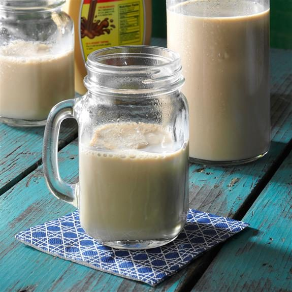 Coffee milk in a mason jar with a handle resting on a blue coaster with white diagonal stripes on a blue wooden table