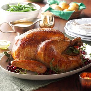 Roasted turkey on a platter beside a gravy boat