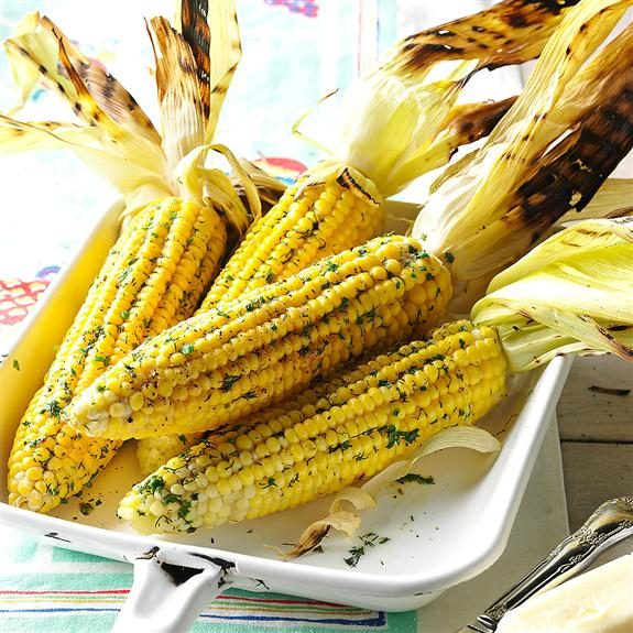 Grilled corn on the cob piled together on a white dish with their seared leaves pulled back behind them