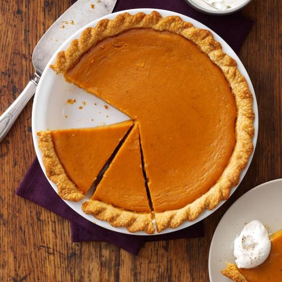 Birds-eye view of a pumpkin pie with one slice missing and two others cut and waiting