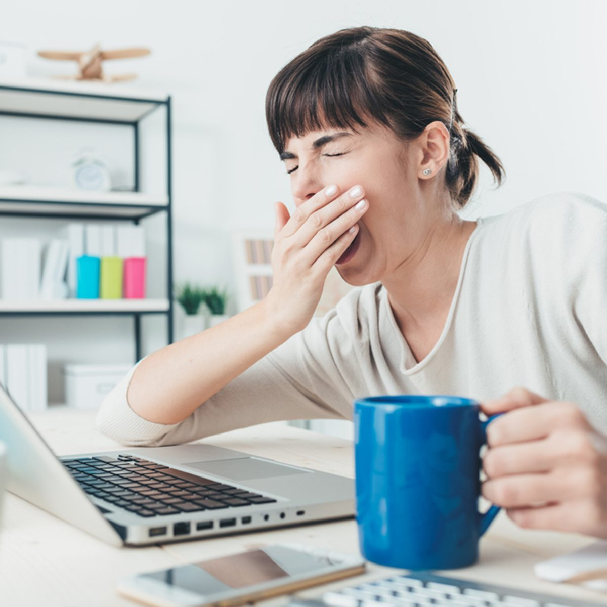 Tired sleepy woman yawning, working at office desk and holding a cup of coffee, overwork and sleep deprivation concept; Shutterstock ID 367741853