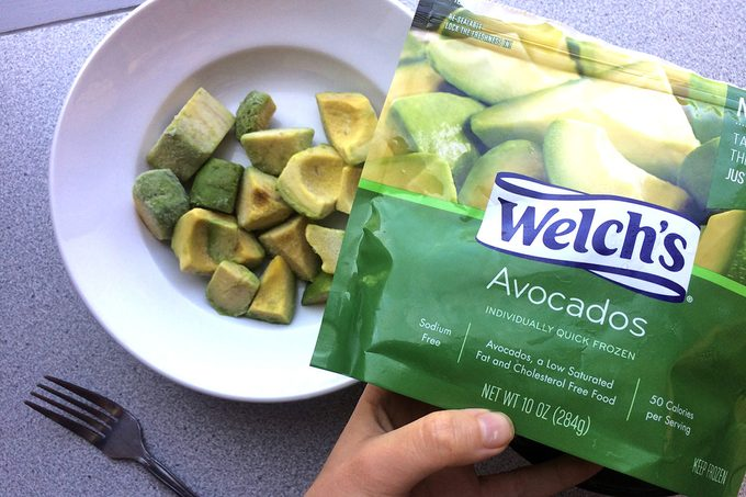 Package of frozen avocados being held up beside a bowl filled with the pieces