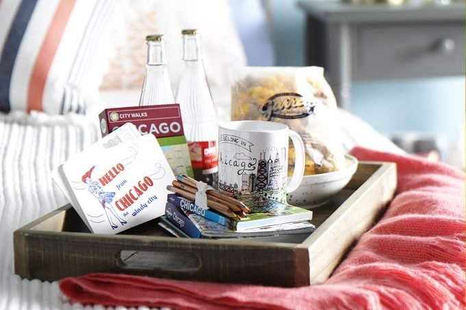Tray on a bed filled with Chicago postcards, guidebooks, maps and regional treats