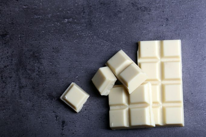 White chocolate pieces on gray background.