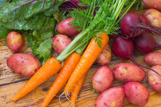 Fresh vegetables (carrots, beets, potatoes) on a wooden surface