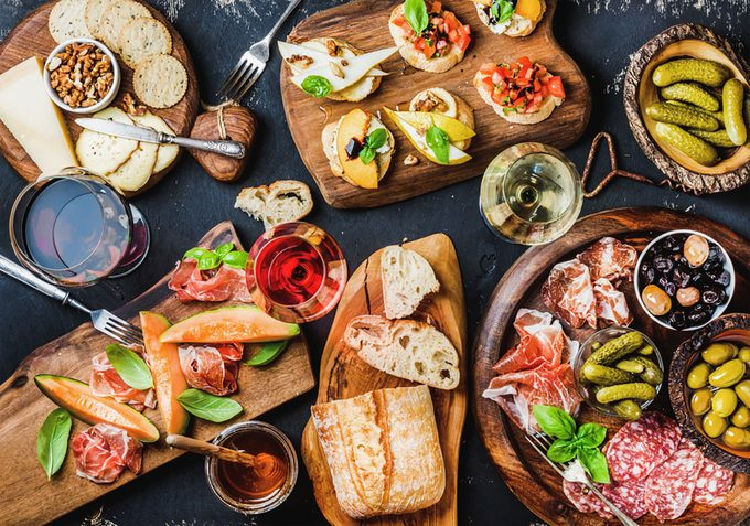 Brushettas, cheese variety, Mediterranean olives, pickles, Prosciutto di Parma with melon, salami and wine in glasses over black grunge background
