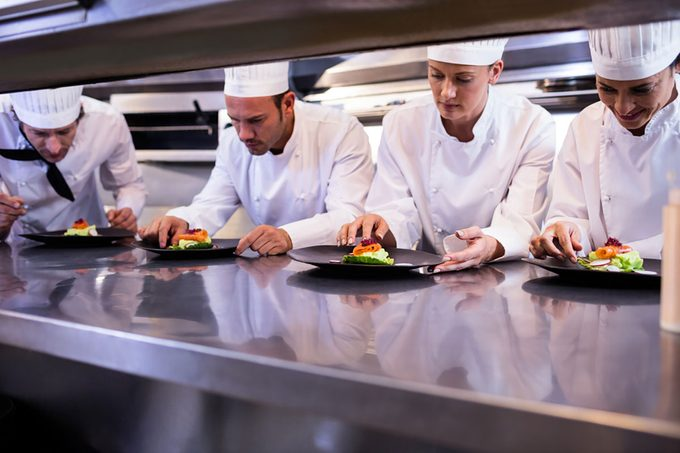 Team of chefs garnishing dishes on commercial kitchen counter