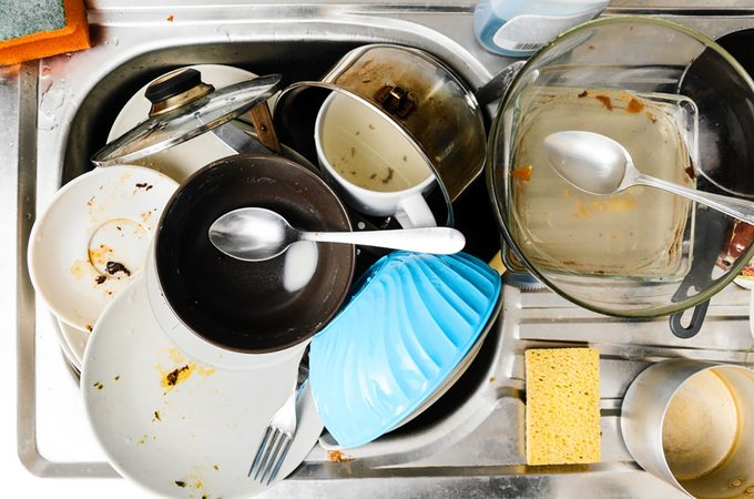 Dirty messy dishes in a sink, view from above