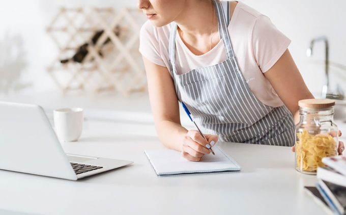 Dedicated hostess making notes in her cookbook