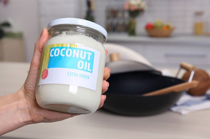 Female hand holding jar with coconut oil