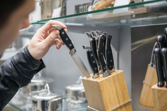 Close up view of customer's hand choosing set of knives for kitchen