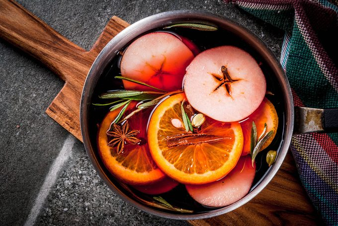 Traditional winter and christmas beverage, mulled wine hot drink with citrus, apple and spices in aluminum casserole on black stone table.
