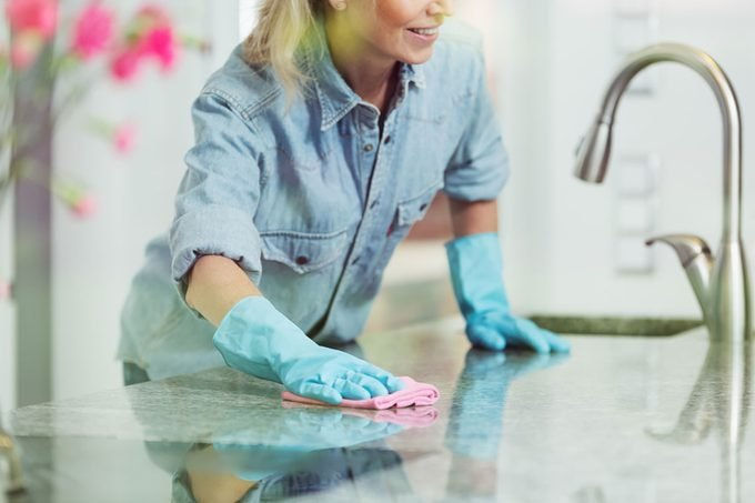 Pedantic woman wiping down kitchen countertop with pink cloth, wearing blue jean shirt and rubber gloves for household cleaning