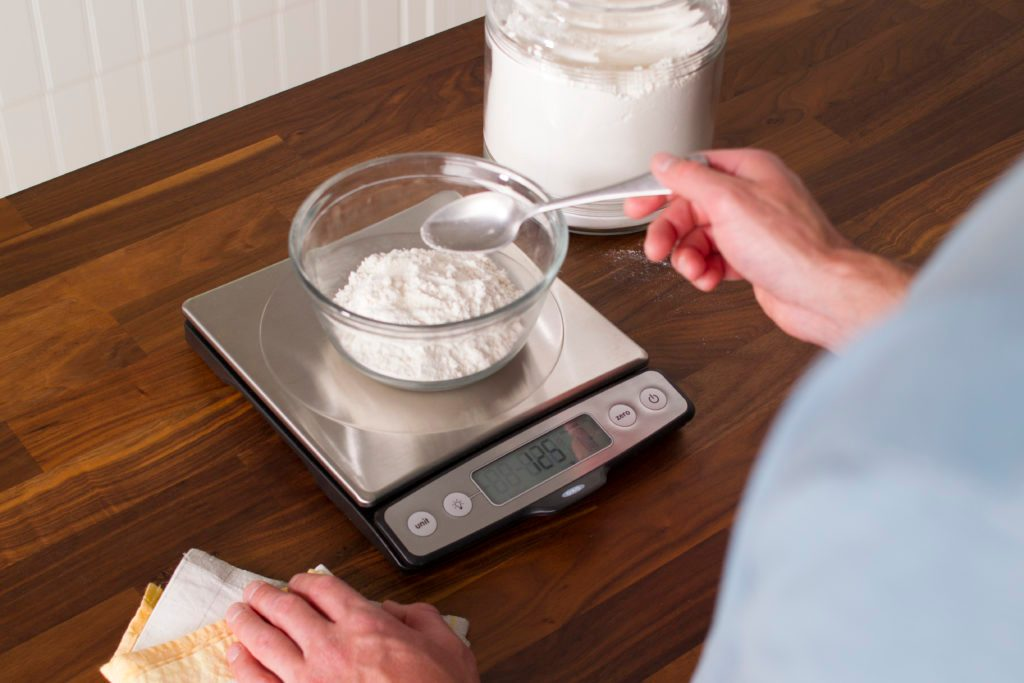 Person using a spoon to scoop flour into a small bowl on a scale