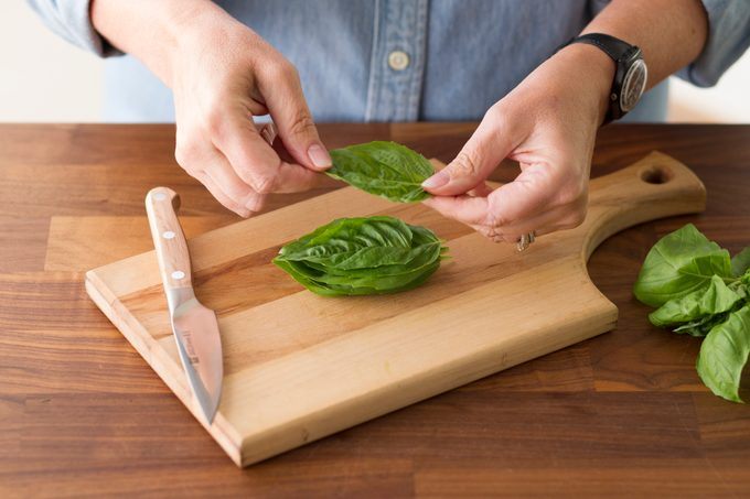 Person stacking basil leaves on a wood cutting board