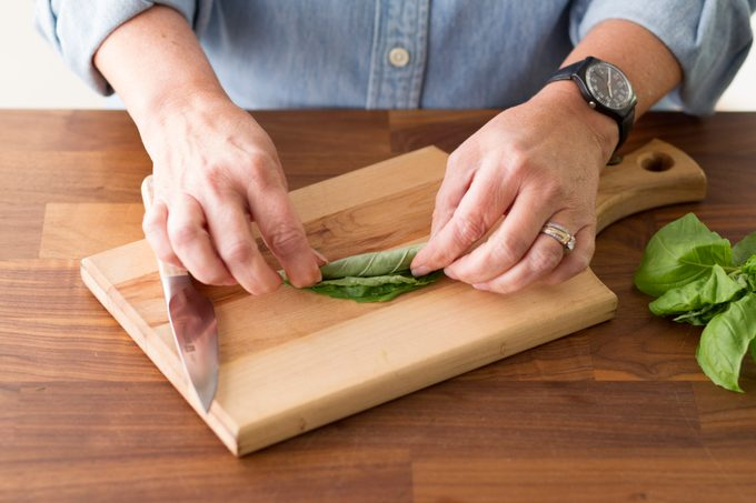 Person rolling the stack of basil leaves together