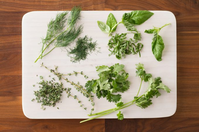 Chopped herbs spread out over a white cutting board