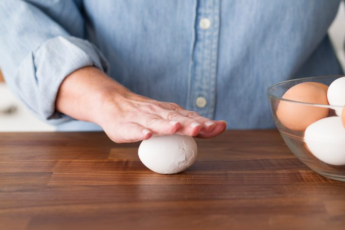 Person using their hand to carefully roll their hard boiled egg against a countertop