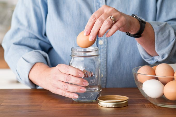 Person lowering an egg into a mason jar with an inch of water