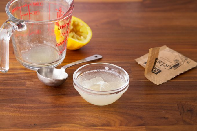 Gelatin mixture in a small glass bowl beside an empty measuring cup, squeezed lemon and empty gelatin packet
