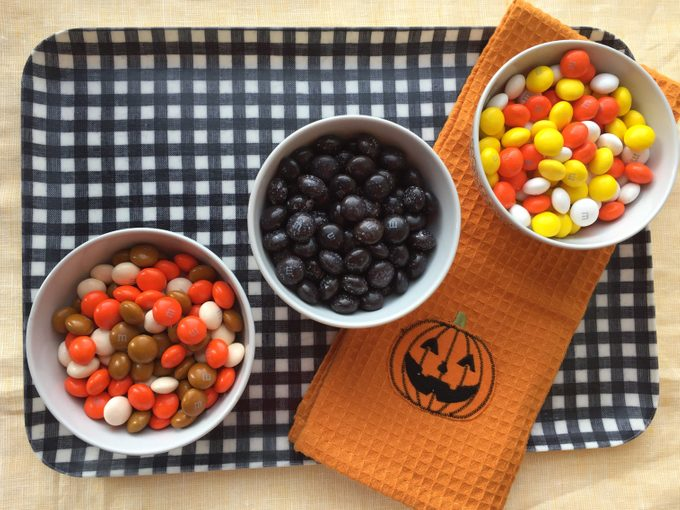 Three bowls of different flavor M&Ms on a checkered platter