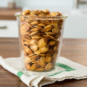 Roasted pumpkin seeds in a glass cup sitting on a wooden table