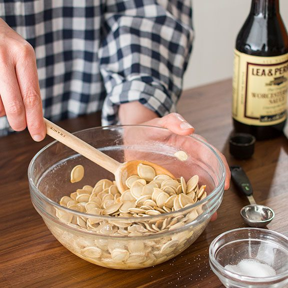 Person stirring seasonings into the seeds with a spatula in a glass bowl