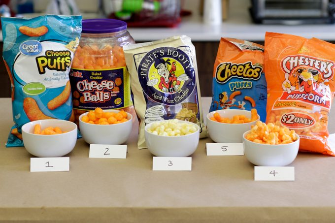 Different brands of cheese puffs lined up on a table with some of each poured into separate numbered bowls