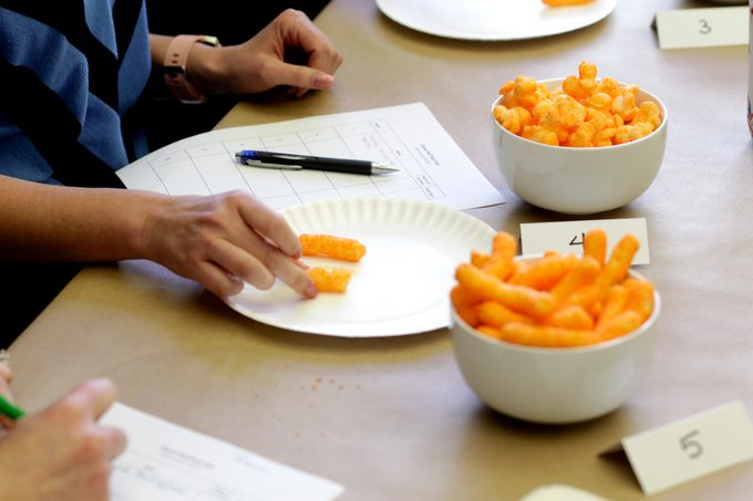 People grabbing cheese puffs from bowls as they take notes