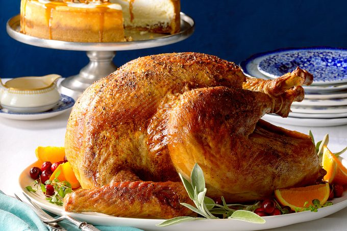 Roasted whole turkey on a platter with a cheesecake behind it against a blue background
