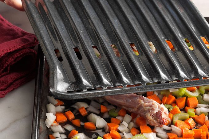 Turkey and diced vegetables on and inside a roasting pan