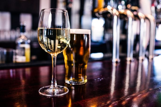 Close up of a glass of wine and a beer in a bar