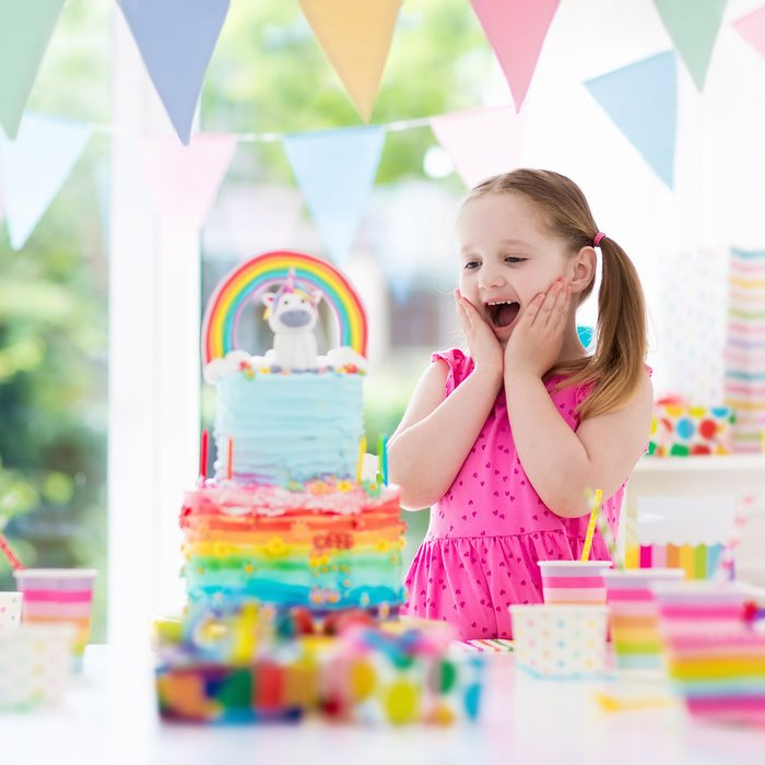 Kids birthday party with colorful pastel decoration and unicorn rainbow cake. Little girl with sweets, candy and fruit. Balloons and banner at festive decorated table for child or baby birthday party.; Shutterstock ID 722010271