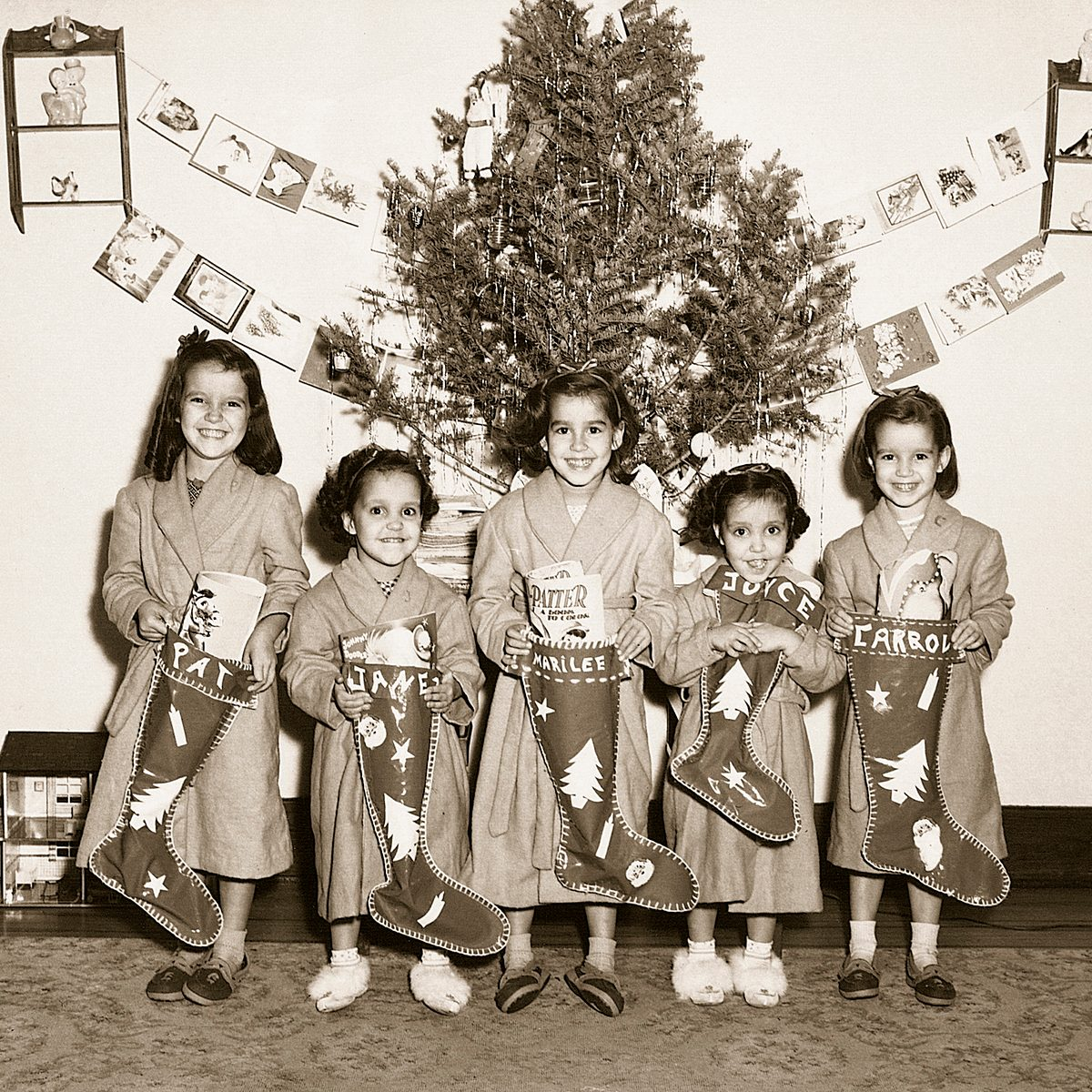 Black and white photo of girls lined up for a photo in front of their Christmas tree with stockings in hand