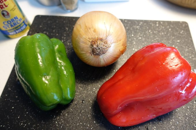 One green pepper, red pepper and onion on a cutting board together