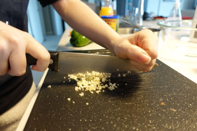 Person using a knife to mince ingredients on a cutting board