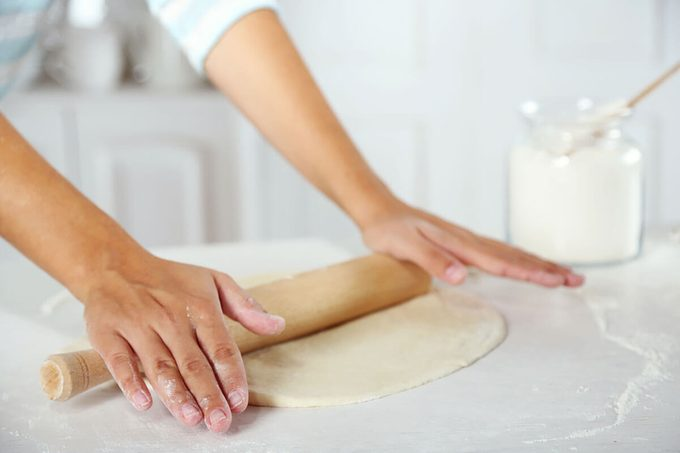 Making dough for apple pie by female hands at kitchen