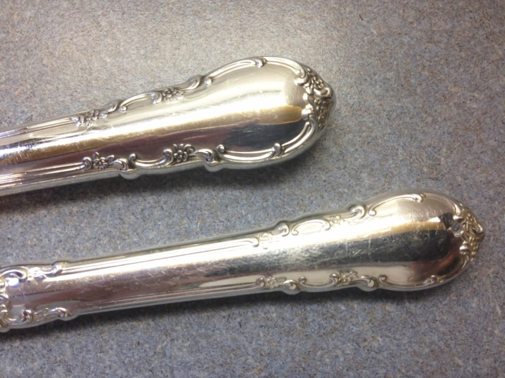 The handles on two pieces of silverware