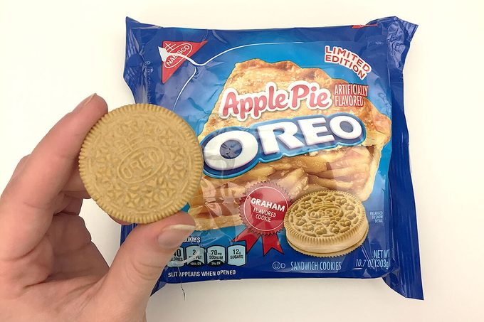 Package of apple pie flavored Oreos with a hand holding a single cookie