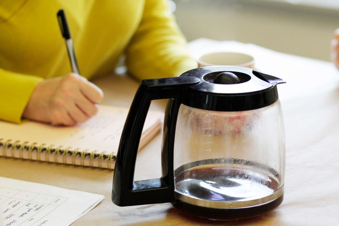 Person in a yellow sweater taking notes behind an empty pot of coffee